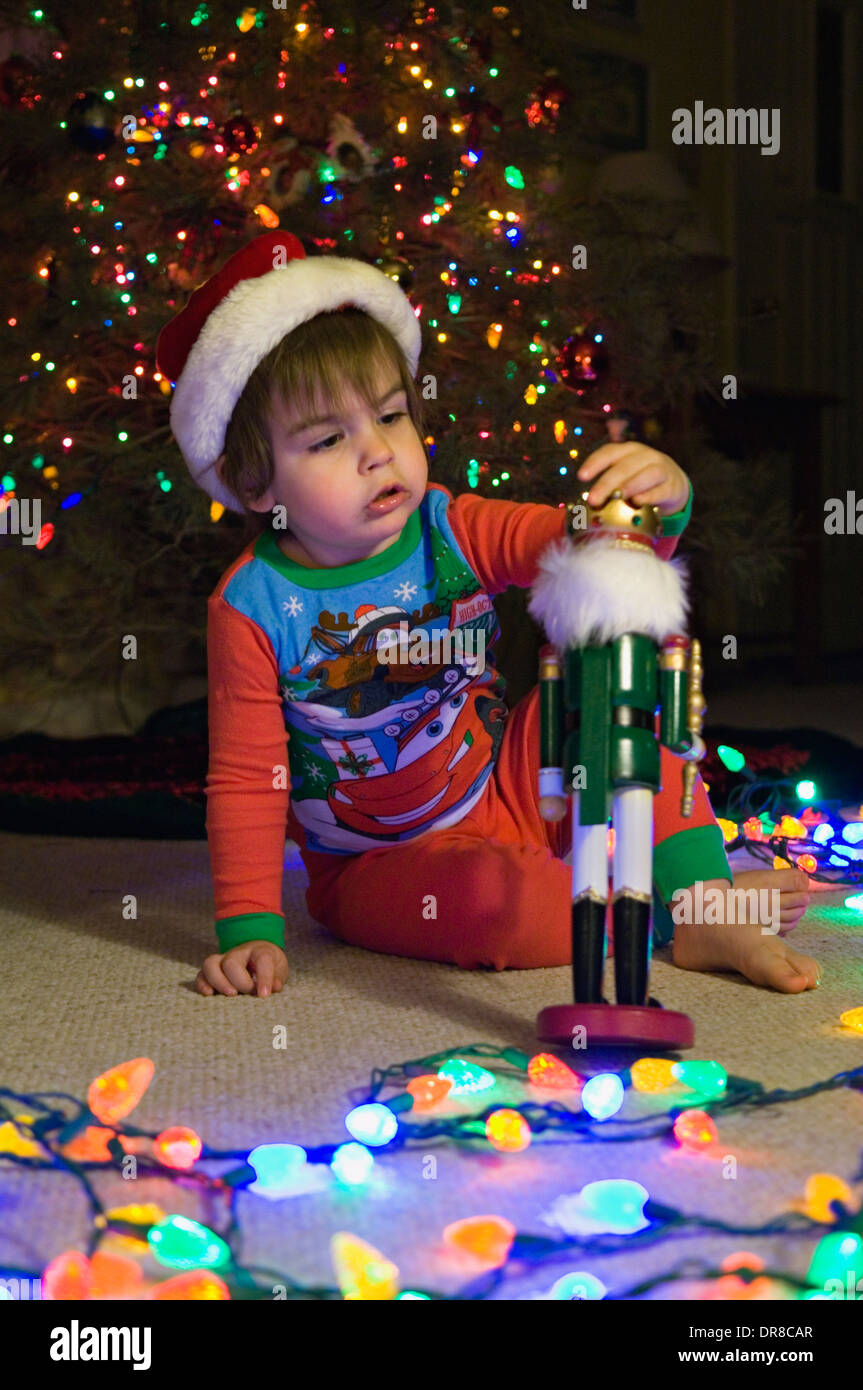 Toddler Playing with Nutcracker beside Christmas Tree - Stock Image