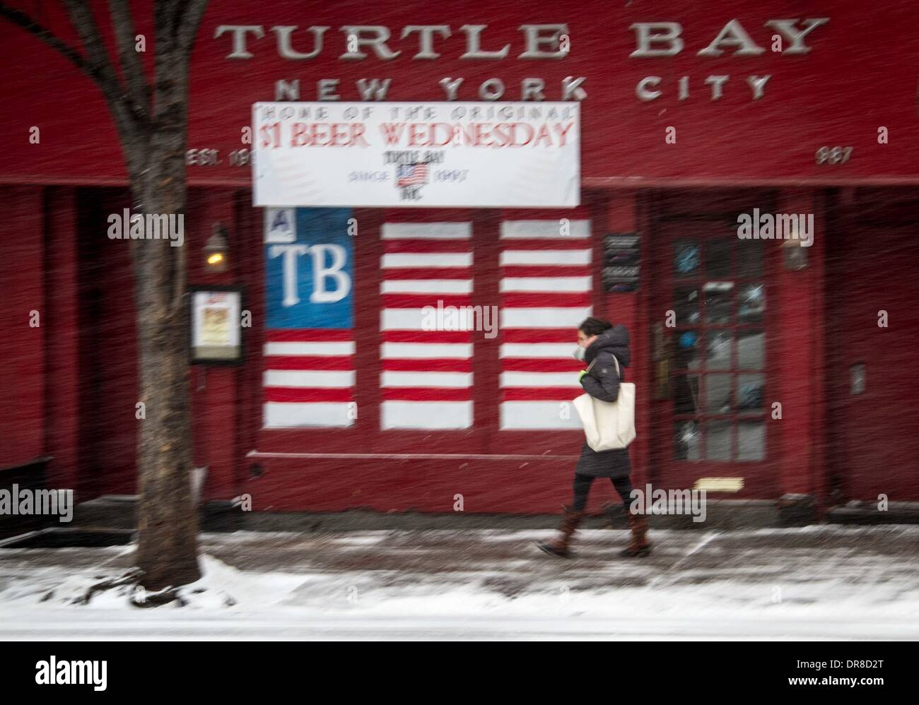 New York, NY, USA. 21st Jan, 2014. A pedestrian walks past a bar during a snowstorm in New York City, the United Stock Photo