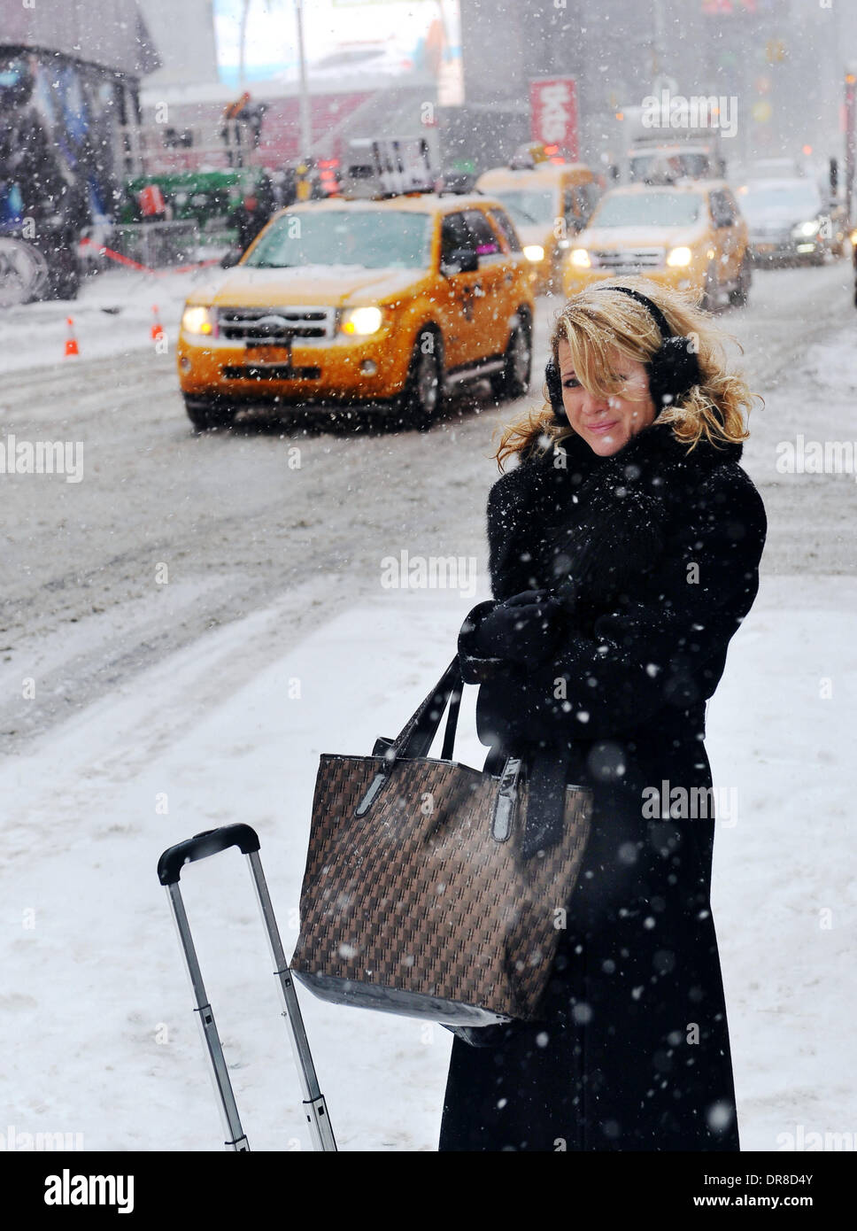 New York, NY, USA. 21st Jan, 2014. A pedestrian waits in snowstorm for signal to pass a street near the Times Square Stock Photo