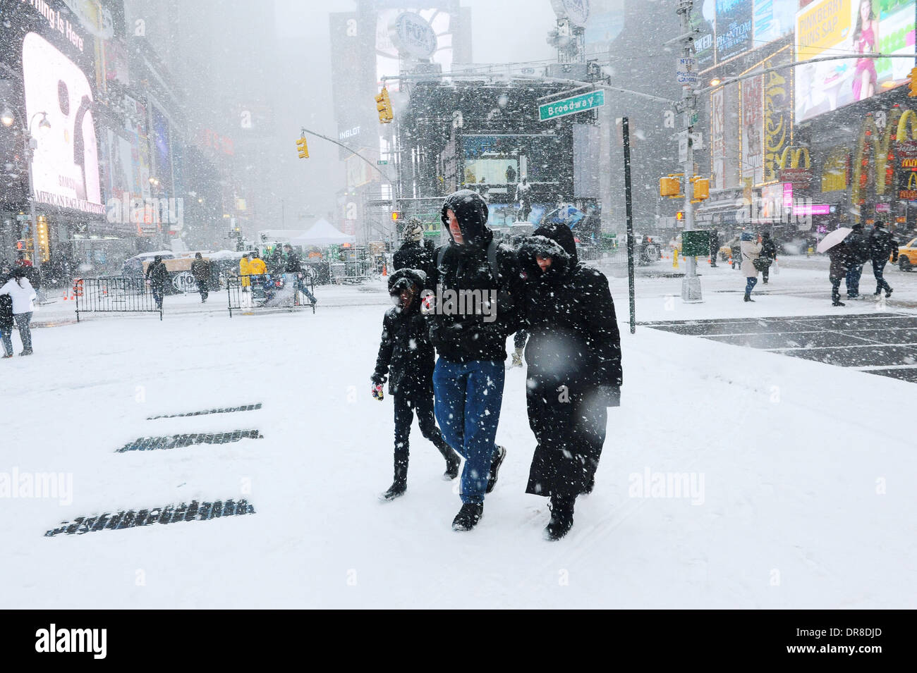 New York, NY, USA. 21st Jan, 2014. Pedestrians walk in snowstorm across the Times Square in New York City, the United Stock Photo