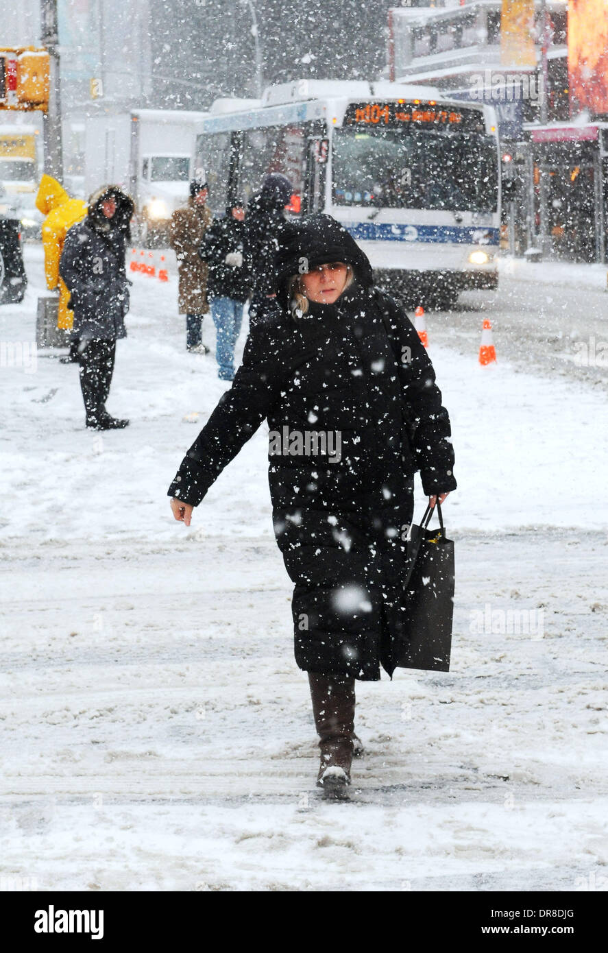 New York, NY, USA. 21st Jan, 2014. A woman walks in snowstorm across a street near the Times Square in New York Stock Photo