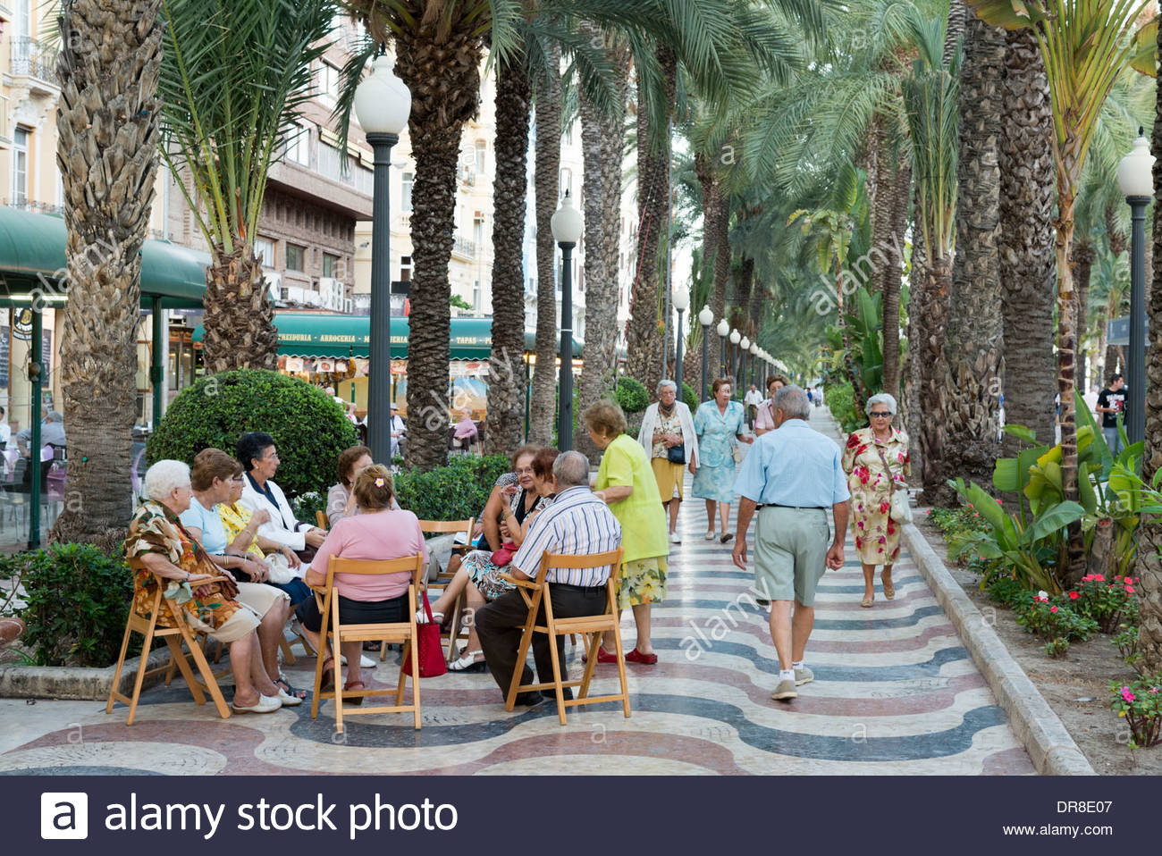 Elderly people sitting on wooden chairs on the Paseo Explanada de Espana, Alicante, Costa Blanca, Spain - Stock Image