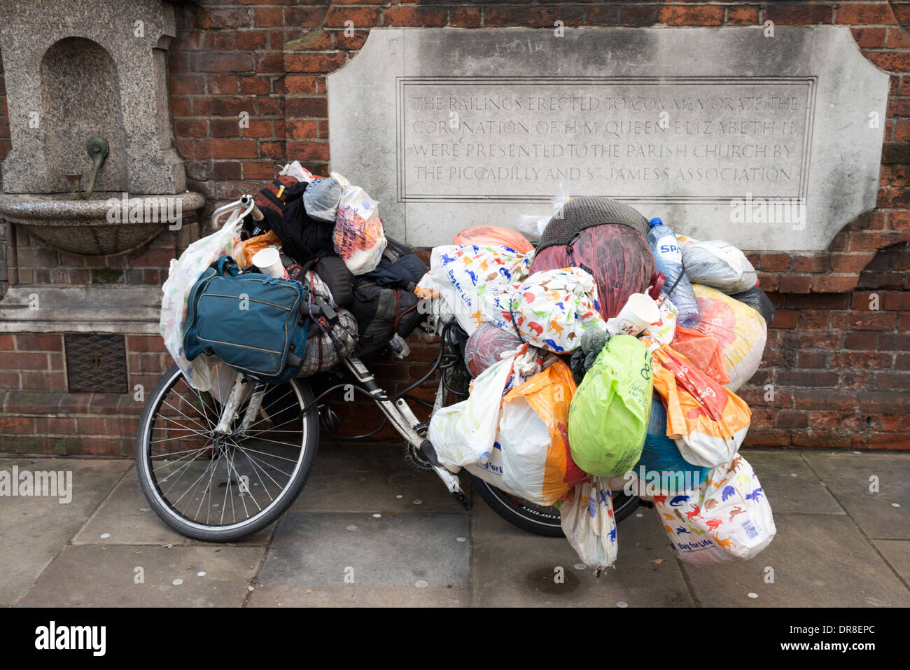 Bicycle with carrier bags of stuff belonging to a homeless person, London, England, UK - Stock Image