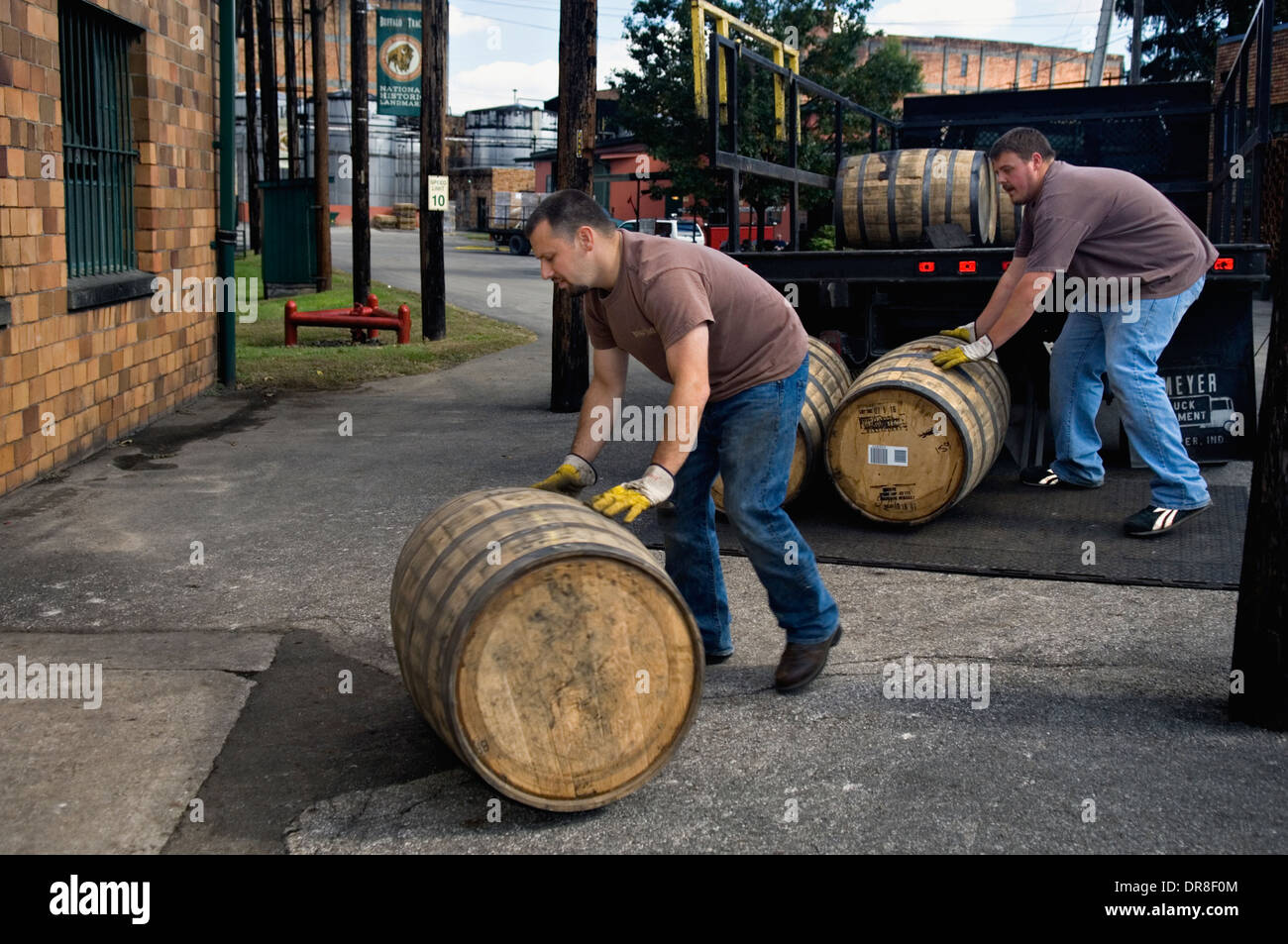 Workers at Buffalo Trace Distillery Rolling Barrels of Bourbon into Storage Building in Frankfort, Kentucky - Stock Image