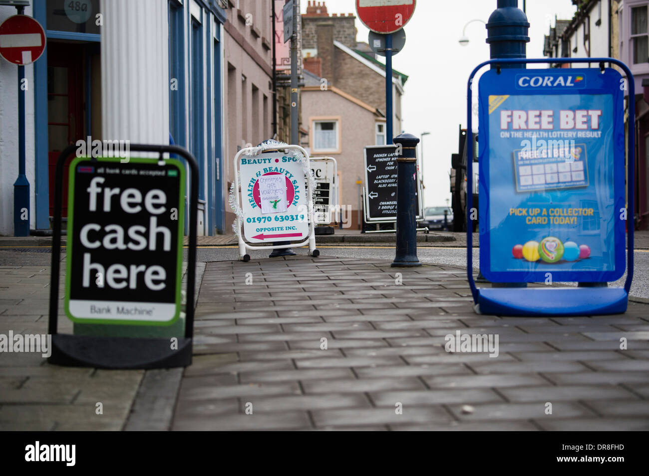 A proliferation of street shop advertising signs causing an obstruction on the pavement Aberystwyth Wales UK - Stock Image