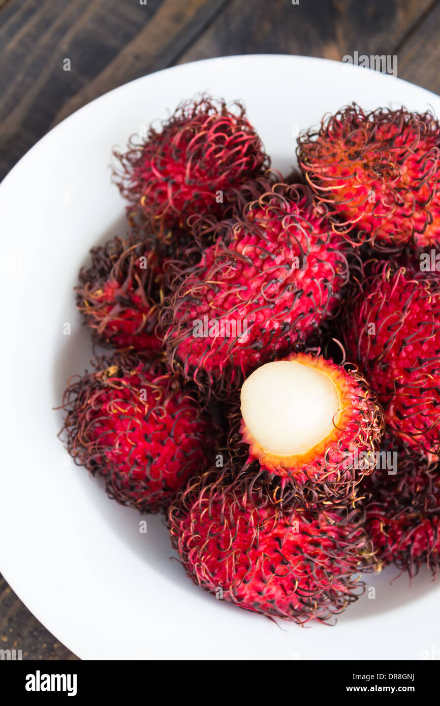 Rambutan is a tropical sweet and sour, white, translucent fruit with a red leathery skin with hairy protuberances. Stock Photo