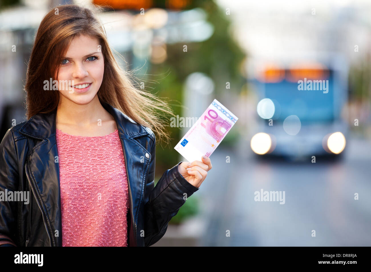Teenage girl at the bus stop holding euro note - Stock Image