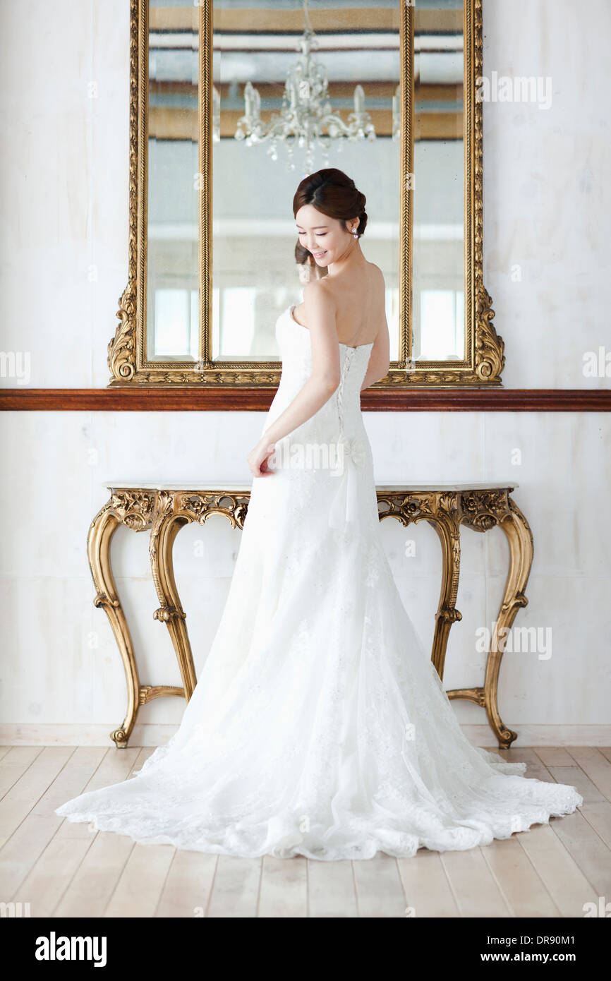 a woman in wedding dress standing in front of mirror Stock Photo ...