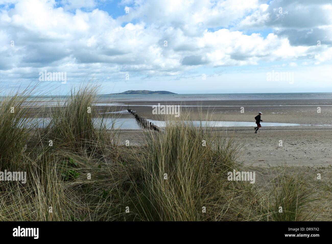 Jogger on the beach at MALAHIDE, Dublin, Ireland, looking across to Lambay Island  - APRIL 2013 - Stock Image