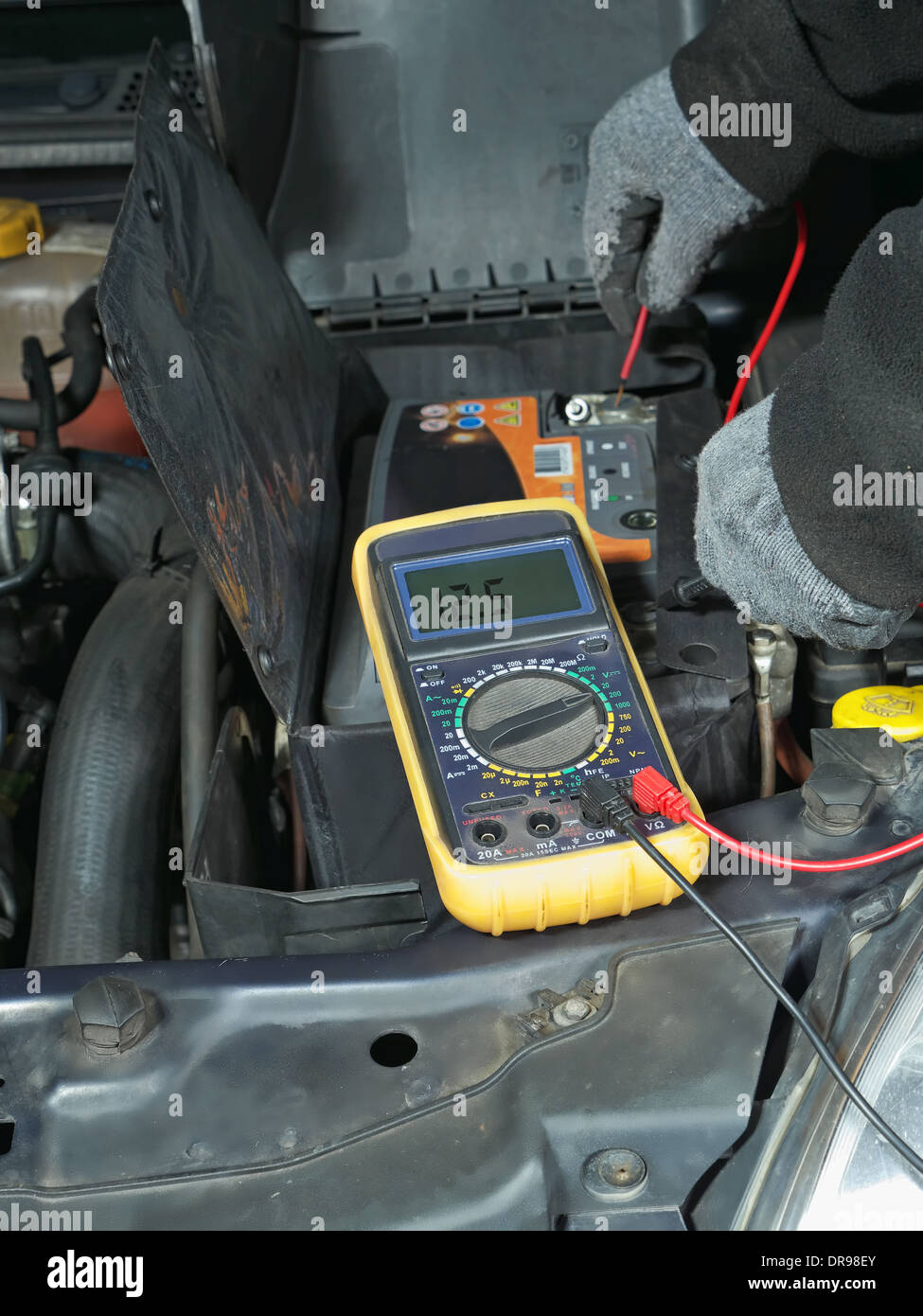 Auto mechanic measuring car battery voltage using multimeter - Stock Image