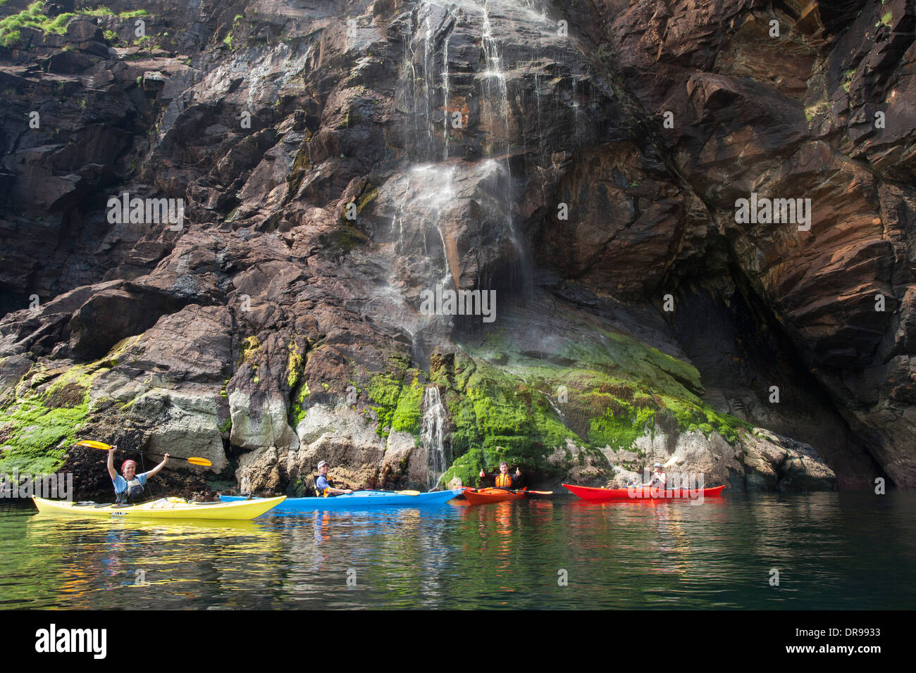 Sea kayaking beneath a waterfall along the Slieve League cliffs, County Donegal, Ireland. - Stock Image