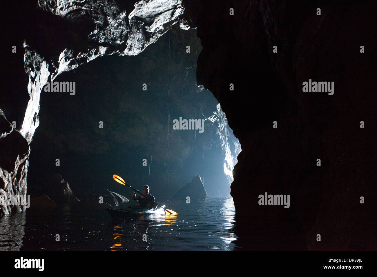 Sea kayaker in a cave beneath the Slieve League cliffs, County Donegal, Ireland. - Stock Image
