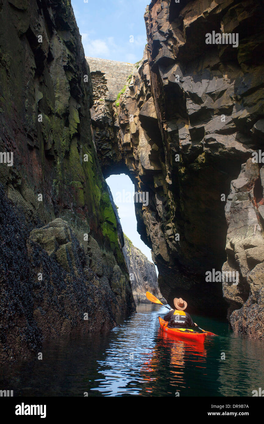 Sea kayaker paddling through an arch on Rathlin O'Birne Island, County Donegal, Ireland. - Stock Image