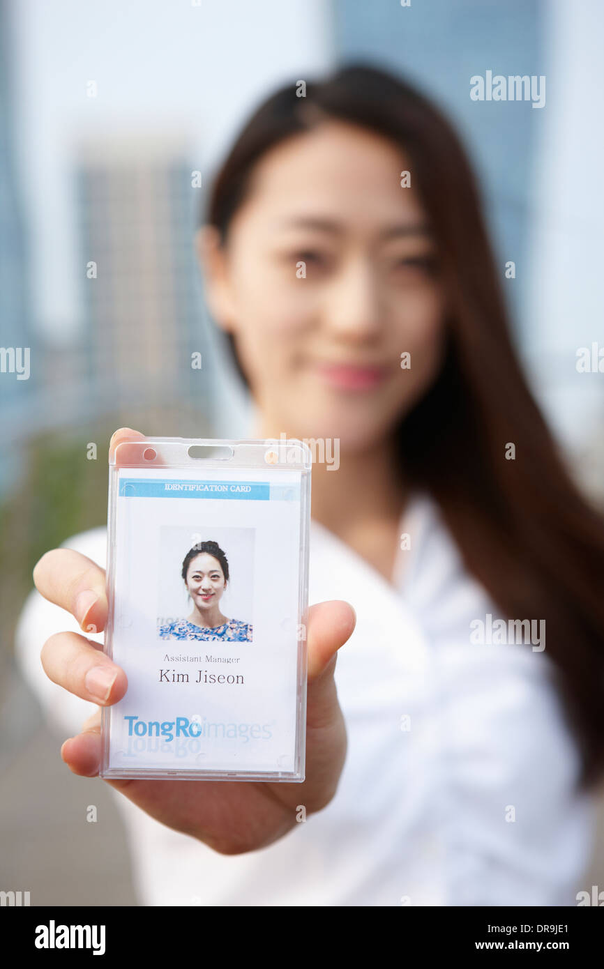 a business woman showing access card - Stock Image