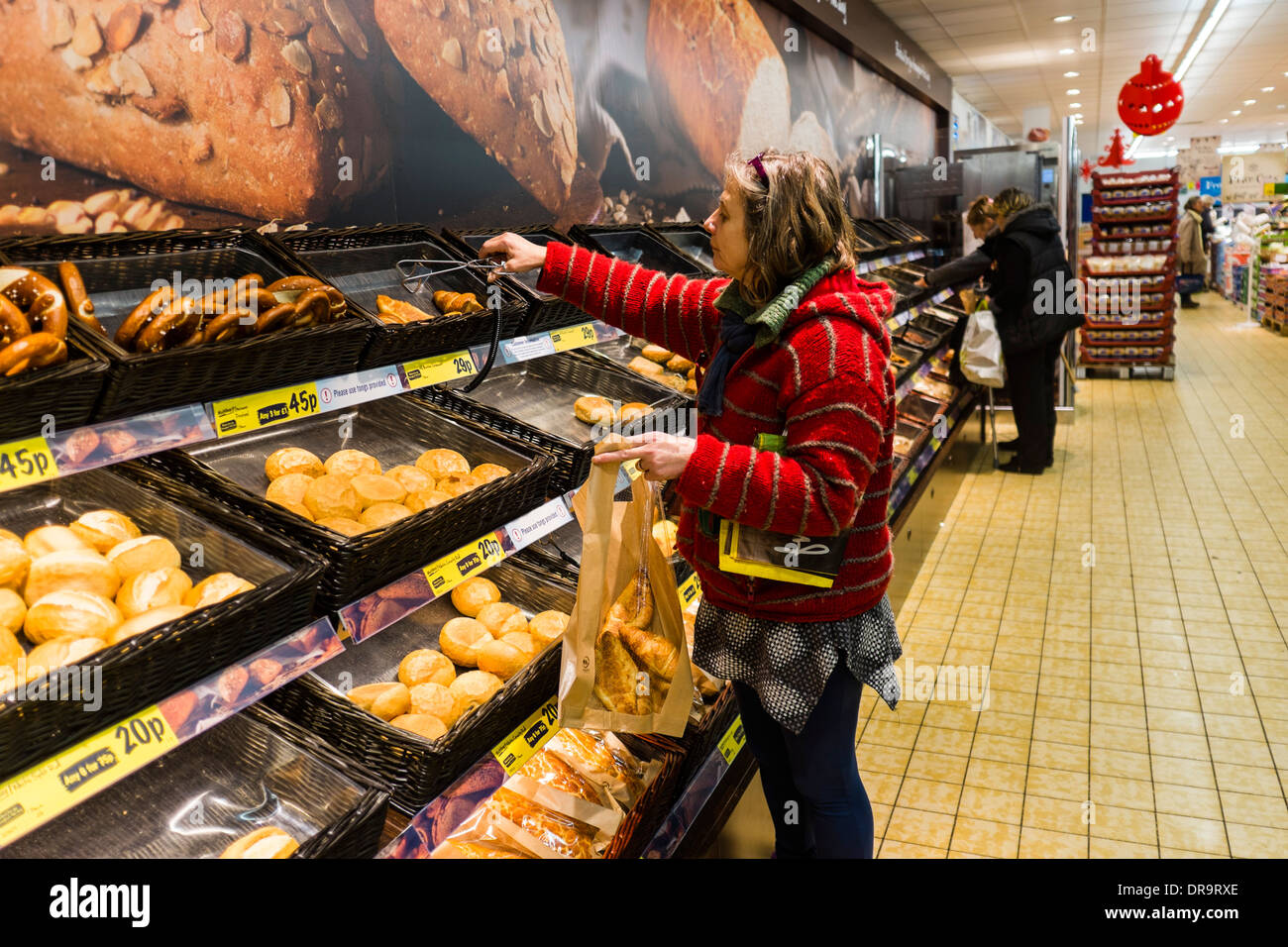 A middle aged woman buying fresh baked in-store croissants and other bakery products in Lidl supermarket, UK - Stock Image