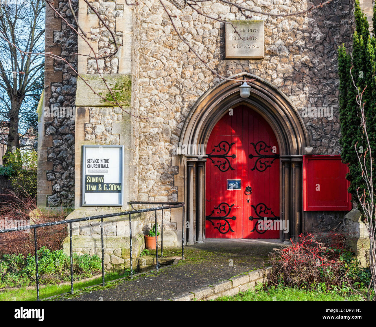 Christ Church stone building and red door - structure is unsafe, dangerous and not in use Teddington - Stock Image