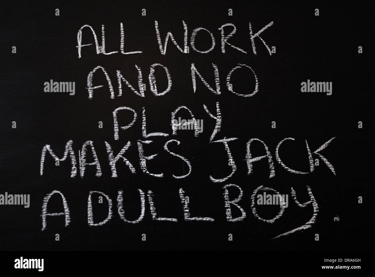 chalk writing- All work and no play makes jack a dull boy - words written on blackboard. - Stock Image