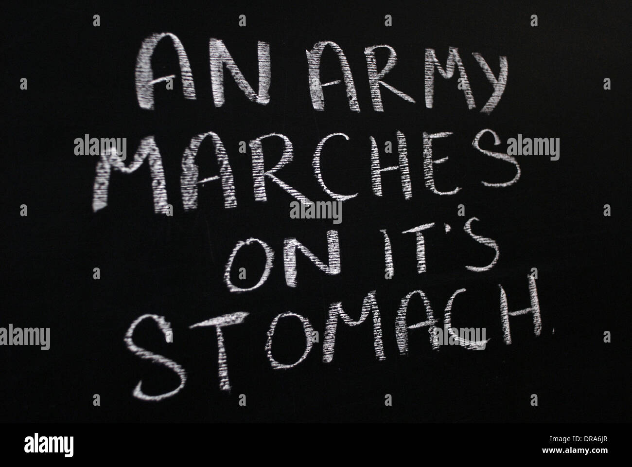 chalk writing- an army marches on it's stomach- words written on blackboard. - Stock Image
