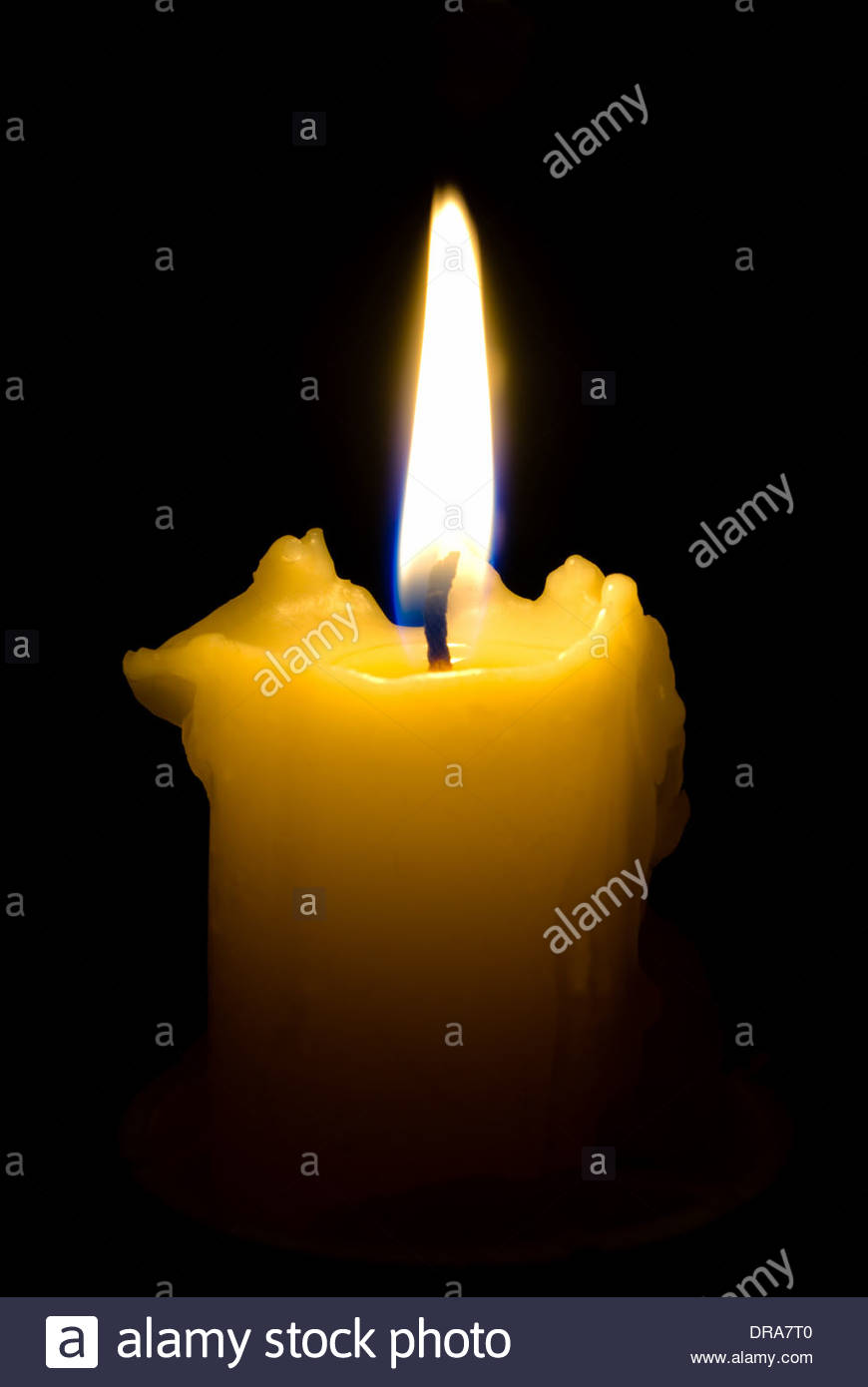 The Burninging candle; close-up; in full darkness; is located in vertically in frame. - Stock Image