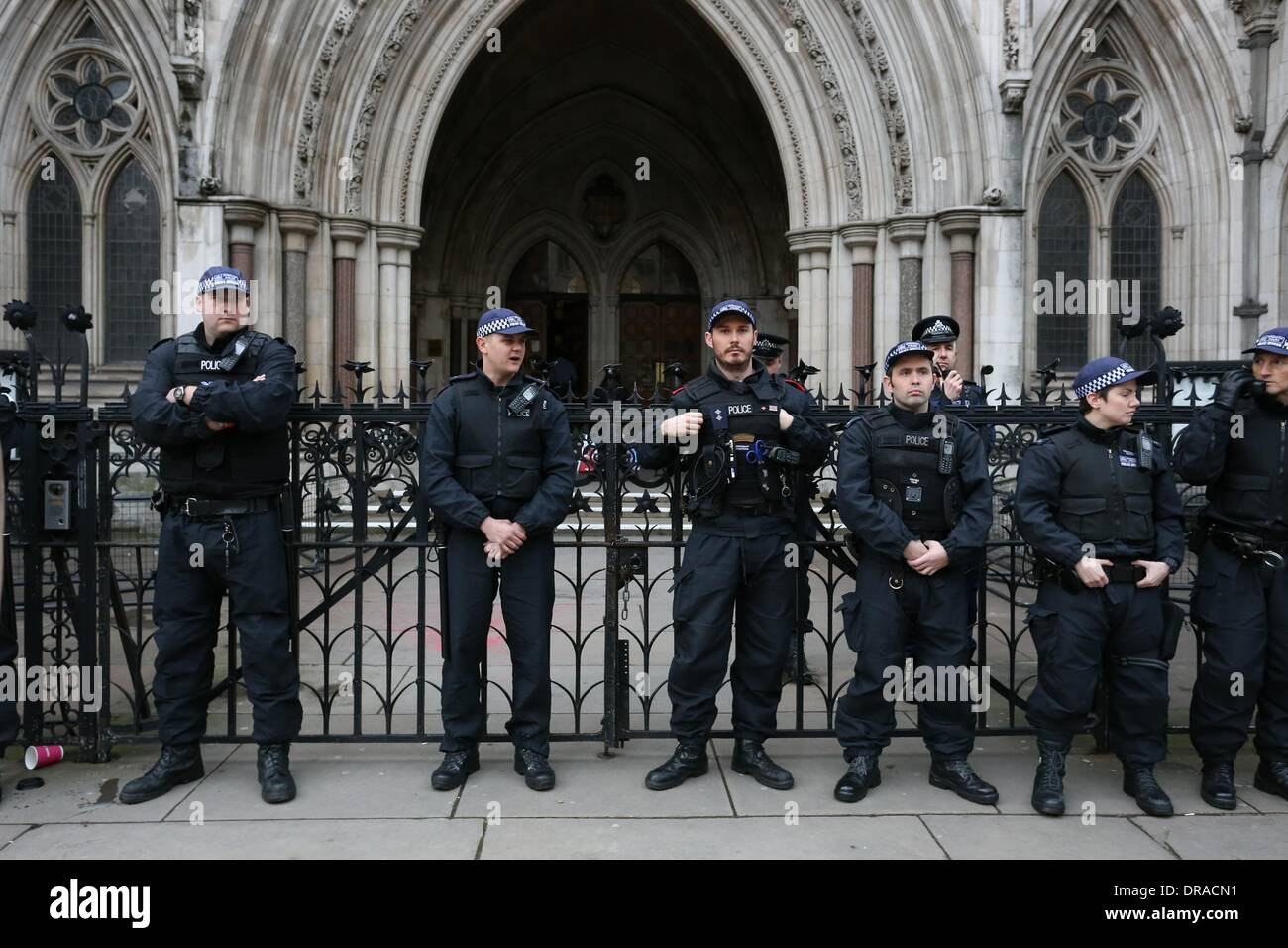 Police stand guard outside the Royal Courts of Justice. Students continued their campaign in support of lecturers - Stock Image