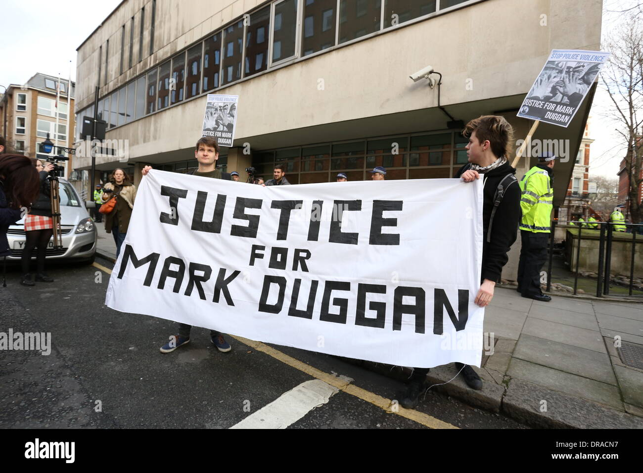 Demonstrators hold a Justice for Mark Duggan banner outside Holborn police station. Students continued their campaign - Stock Image
