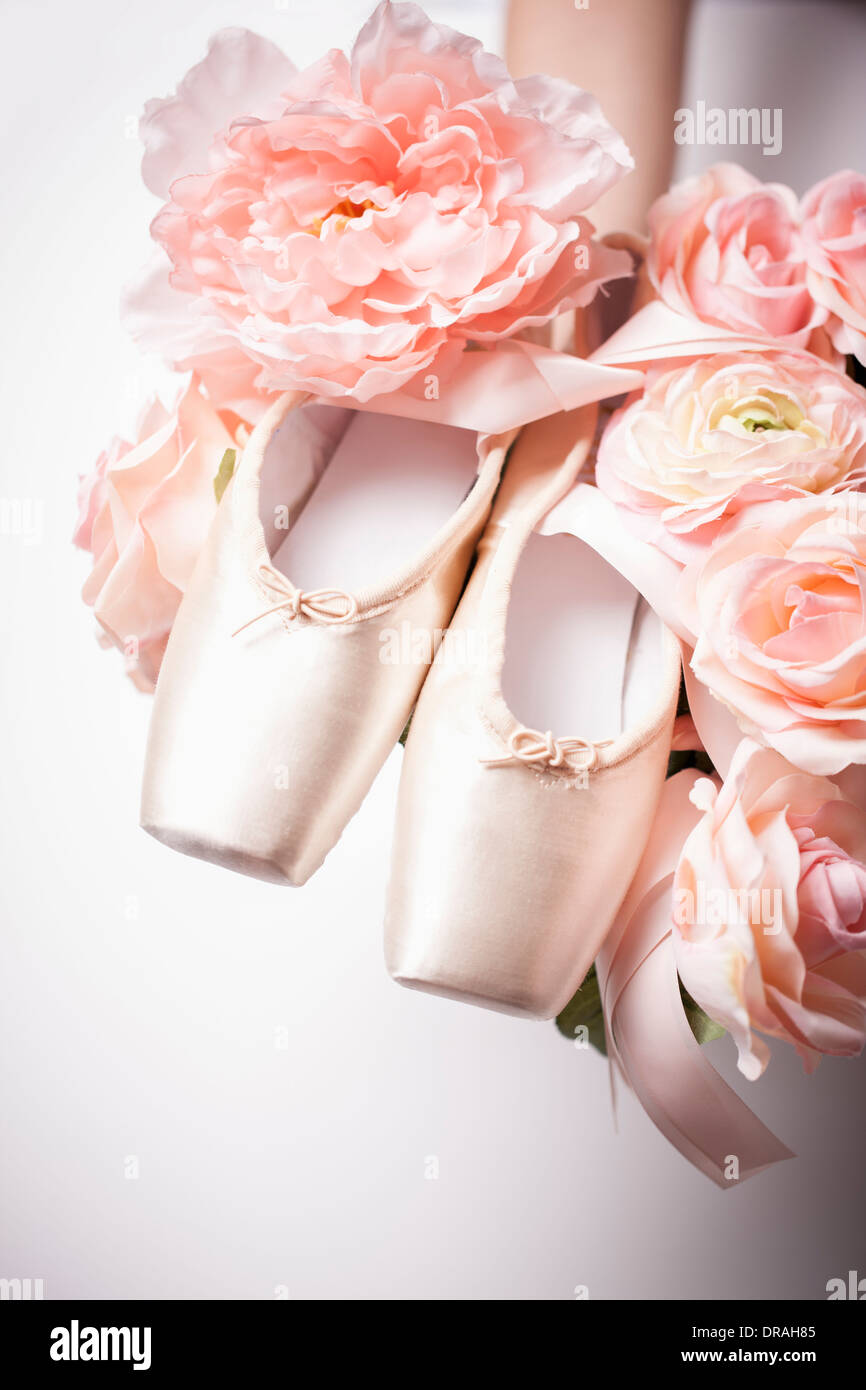 a1fa816d372 a woman holding ballet shoes on flowers Stock Photo  66001269 - Alamy