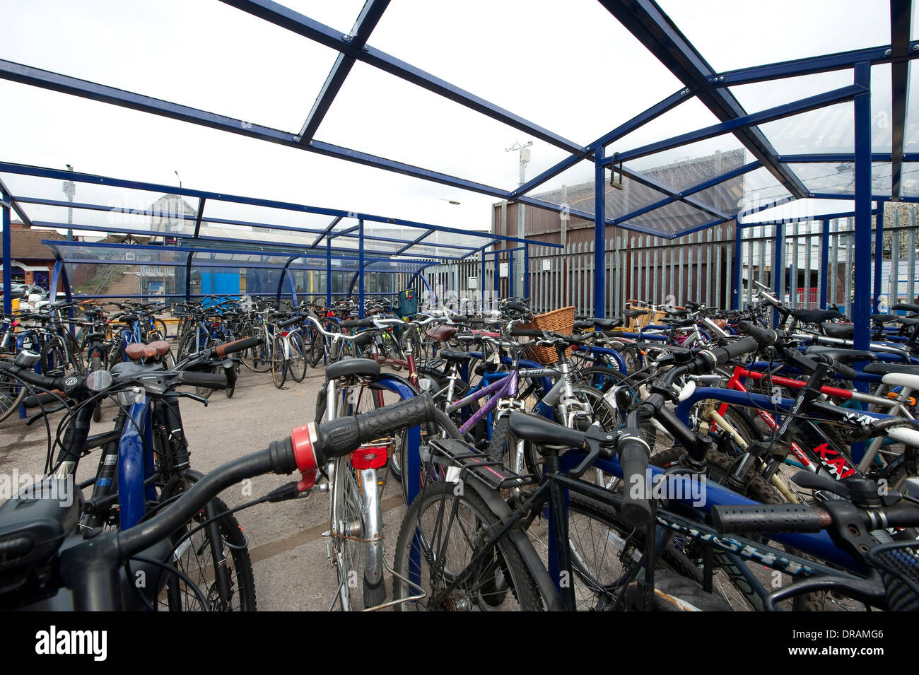 Bicycles parked safely in secure cycle parking area outside a railway station in England. - Stock Image