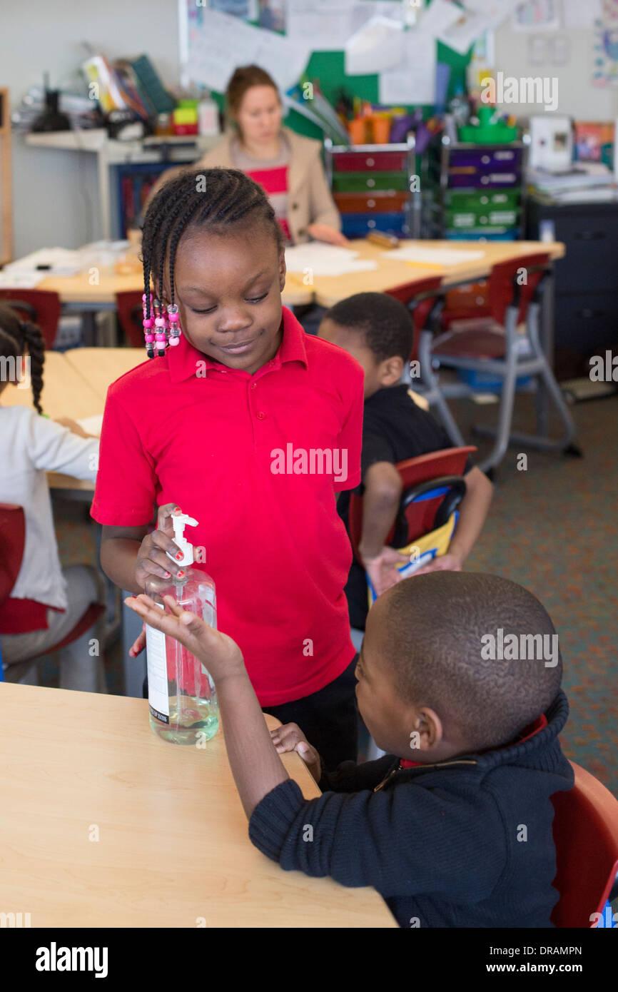 Students use hand sanitizer in kindergarten classroom. - Stock Image
