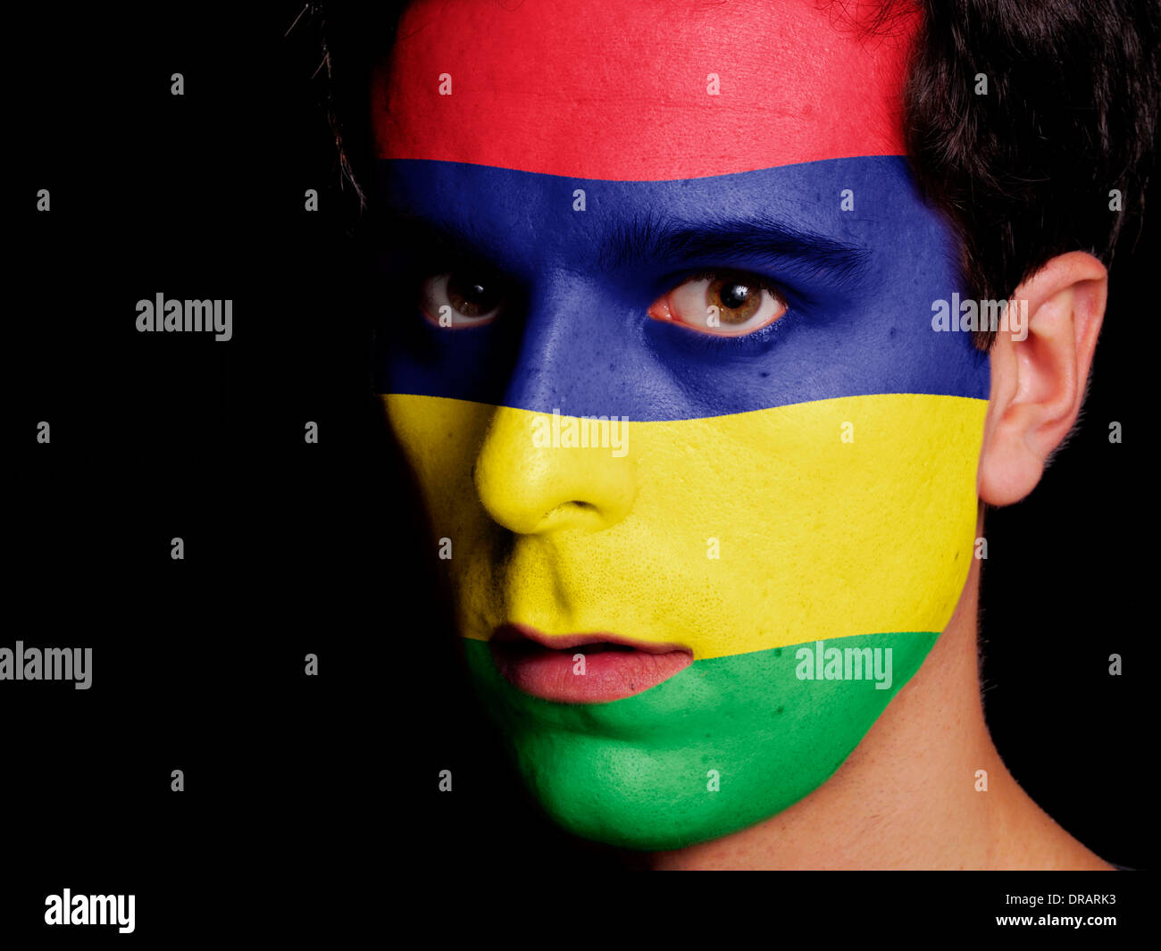 Flag of Mauritius Painted on a Face of a Young Man - Stock Image