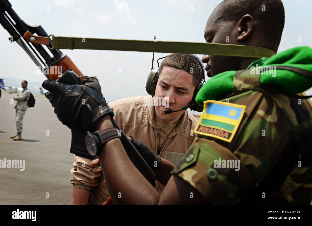 Rwandan soldiers have their weapons inspected before boarding a US Air Force C-17 Globemaster III aircraft in support of an African Union effort to quell violence in the Central African Republic January 19, 2014 in Kigali, Rwanda. - Stock Image
