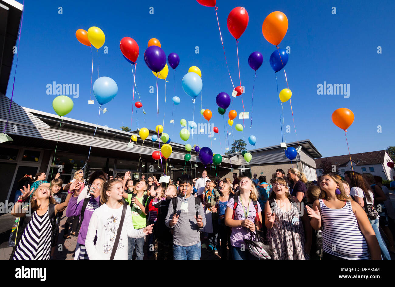 Young students let balloons with their wishes attached rise to the blue sky at the start of their new school year - Stock Image