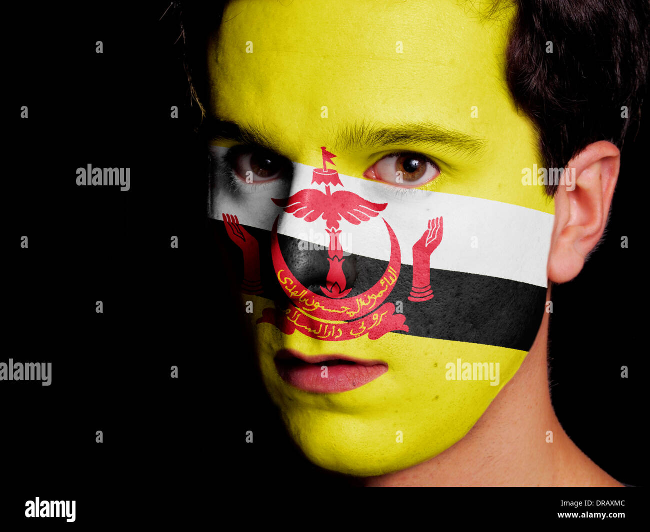 Flag of Brunei Painted on a Face of a Young Man - Stock Image