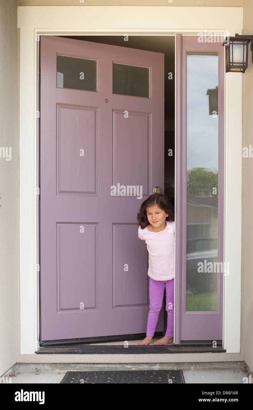Little girl with open door at the entrance of house Stock Photo