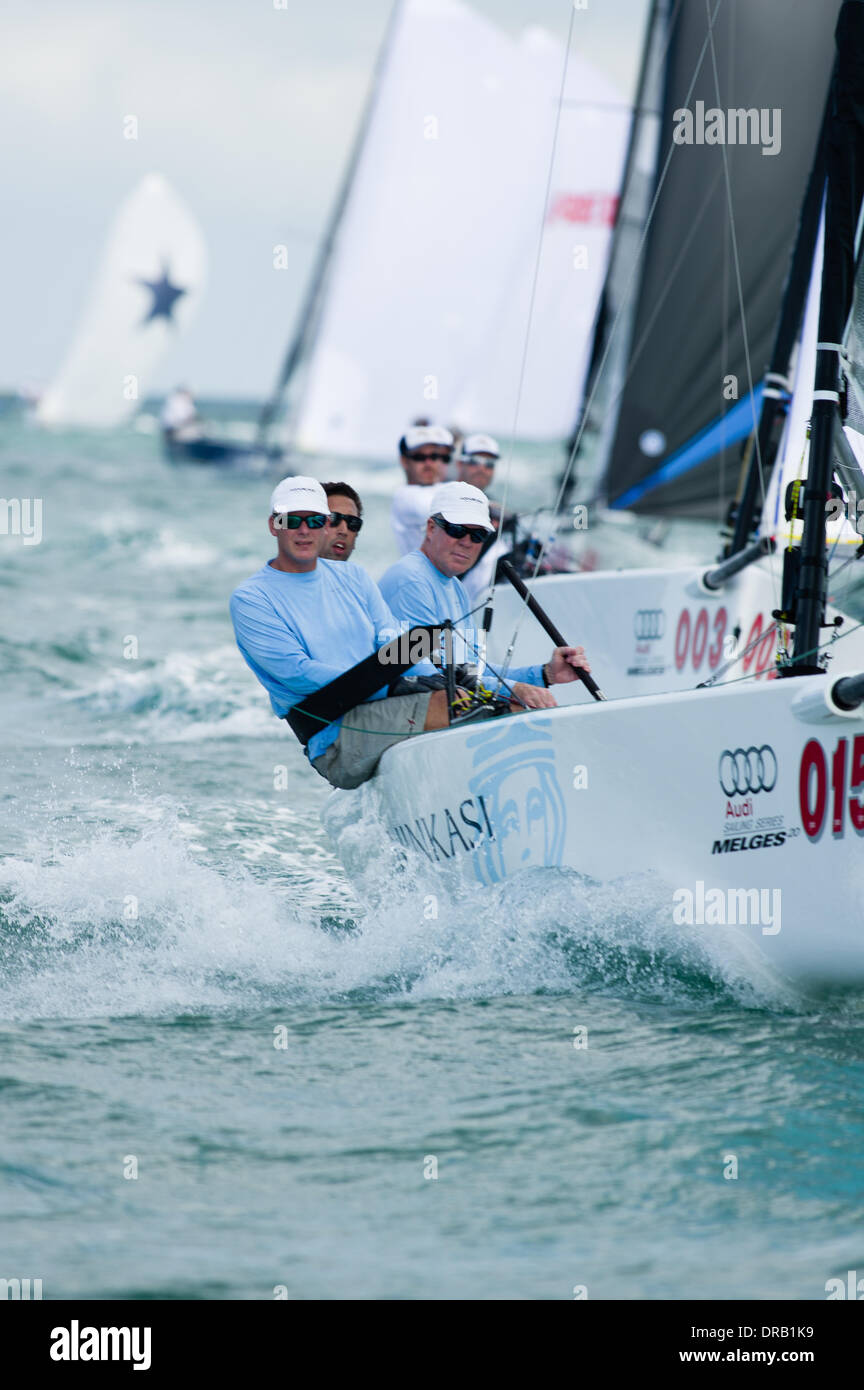 Key Largo, USA, December 12, 2013 - John Taylor of Jupiter, FL skippered Ninkasi to his first-ever win at the first Melges 20 World Championships in Key Largo, FL.  Tactician Bill Hardesty is pictured farthest forward and Joey Mello is trimming the headsail. - Stock Image