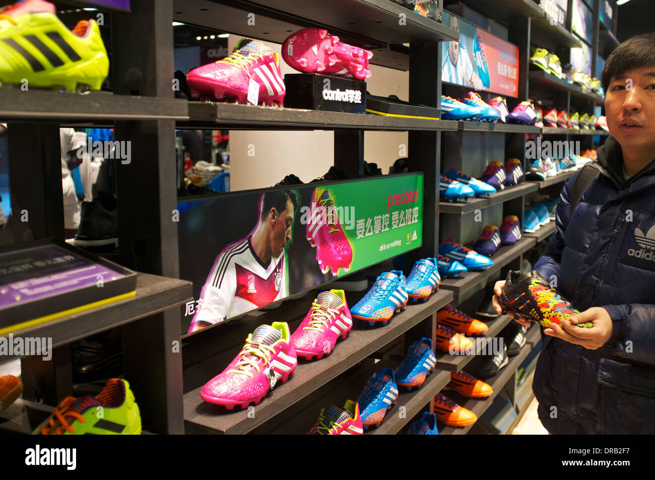 People shop at Adidas outlet in Beijing, China. 21-Jan-2014 - Stock Image