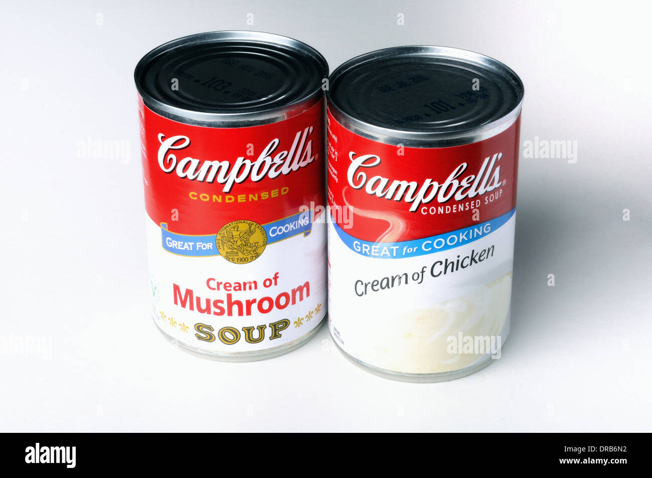 Tins of Campbell's 'cream of' soups on a neutral background. - Stock Image