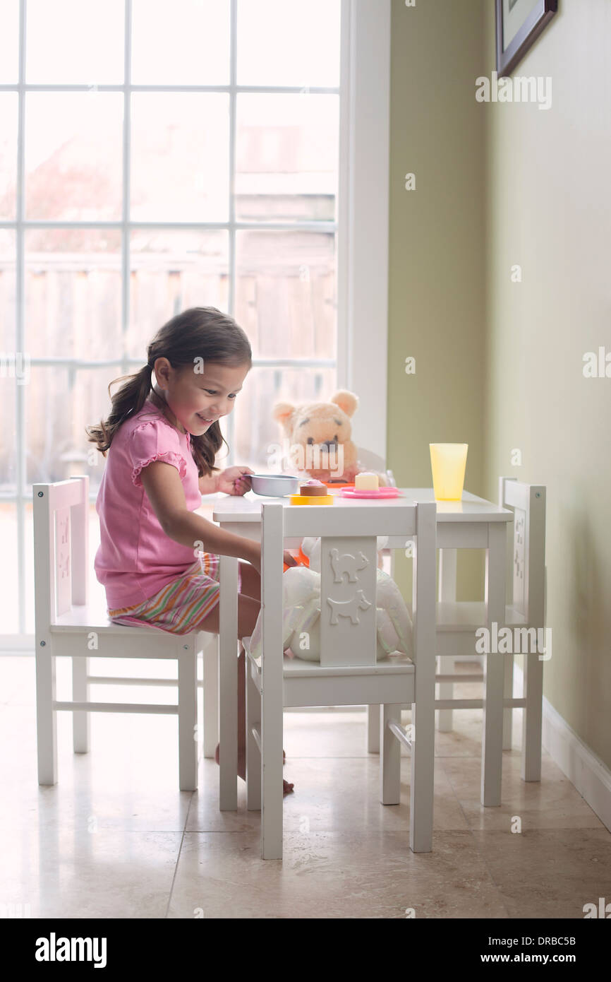Happy little girl feeding teddy bear at dining table - Stock Image