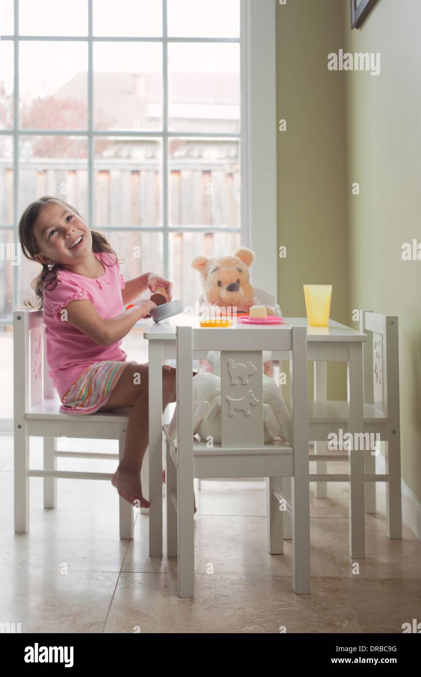 Cheerful little girl with pretend game at dining table - Stock Image