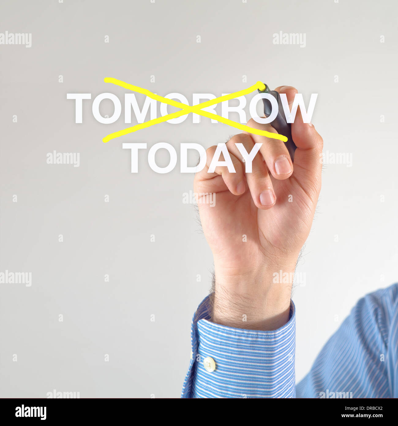 Businessman crosses off tomorrow for TODAY with yellow marker pen on the screen - Stock Image