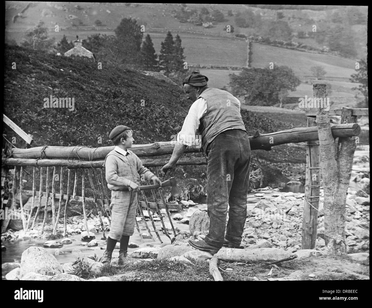 Man and a boy repairing a stream fence, taken around 1906. Langdale, Lake District, Cumbria (then Westmorland), England. The photograph is unattributed, but is probably by the well-known photographer Percy Lund. - Stock Image