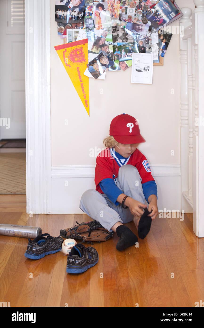 Little baseball player removing socks on wooden floor. - Stock Image
