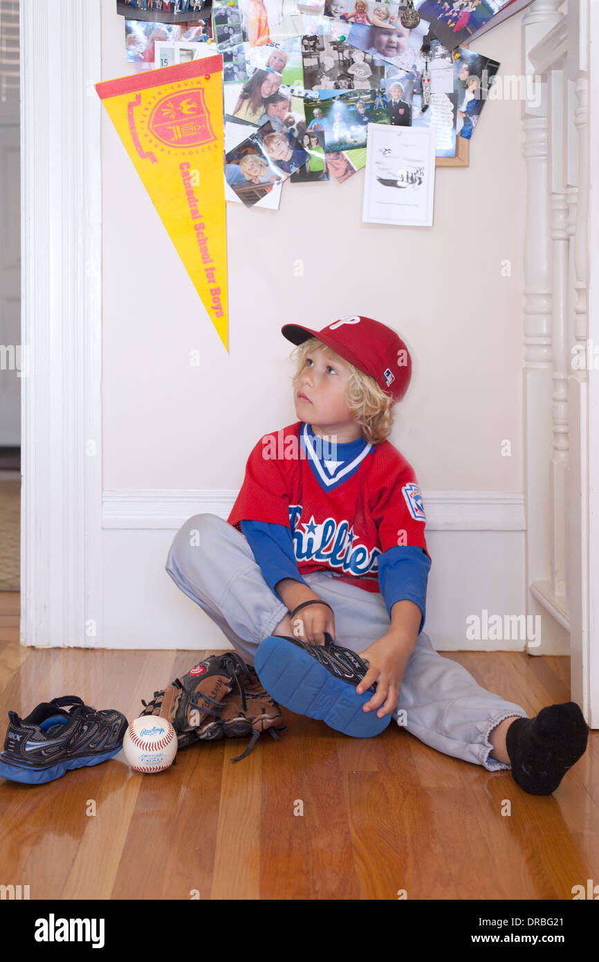 Curious little boy removing baseball boot on wooden floor - Stock Image