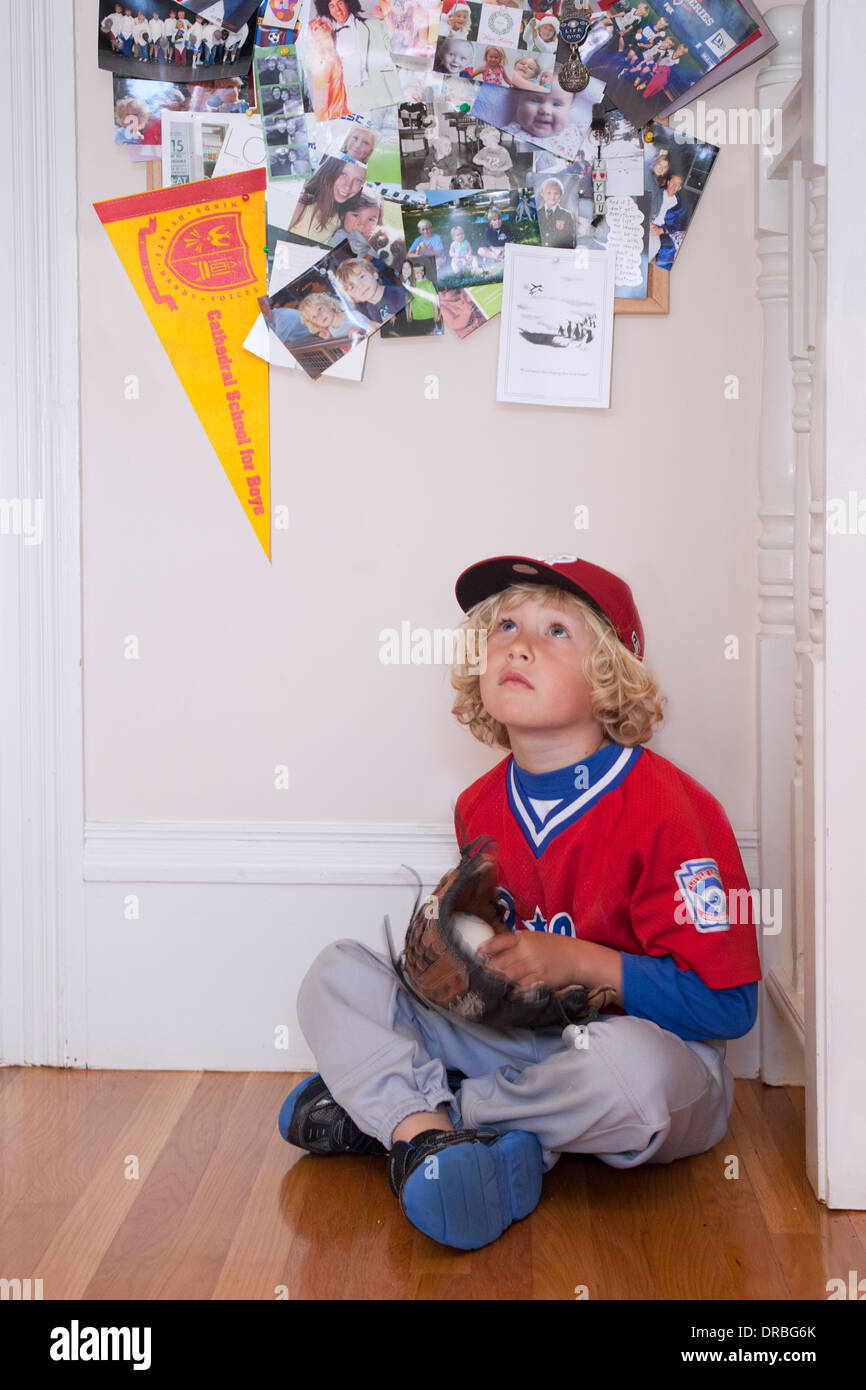Curious little boy sitting on wooden floor with baseball gloves and ball - Stock Image