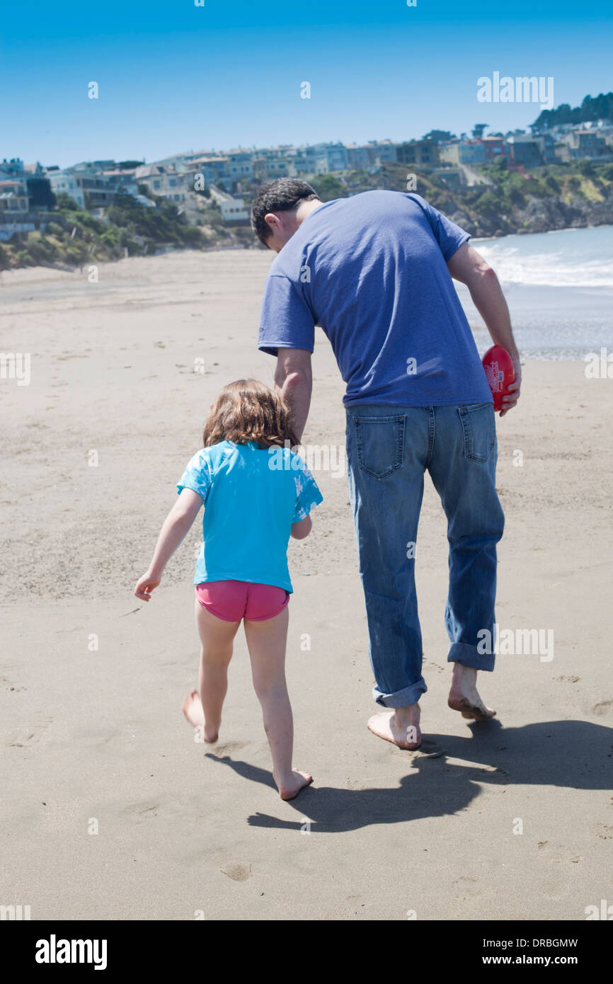Rear view of father and daughter at beach - Stock Image