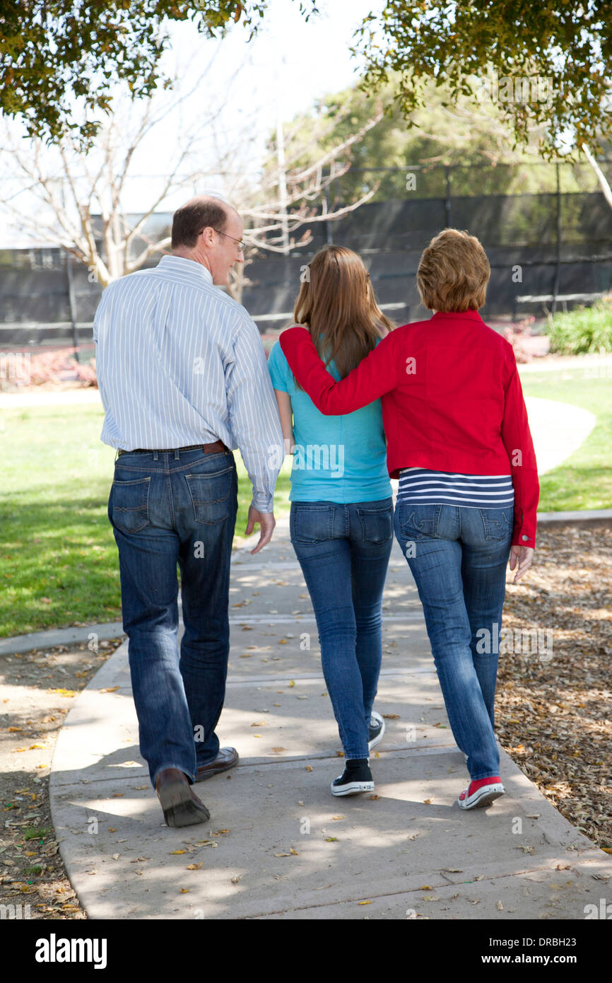 Rear view of parents with daughter walking down a path. - Stock Image