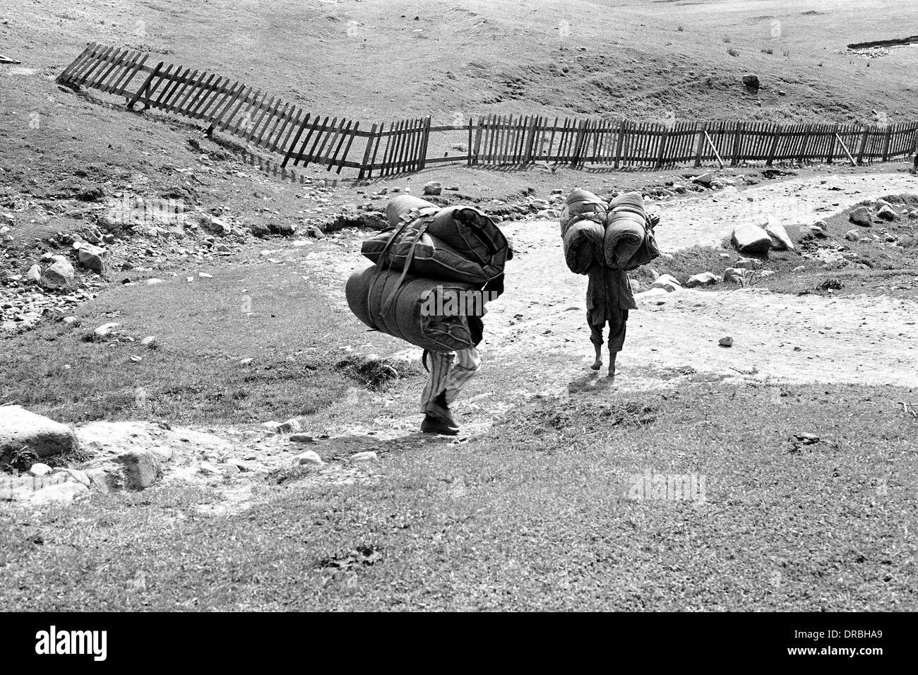 Two porters carrying heavy luggage, Gulmarg, Jammu and Kashmir, India, 1971 - Stock Image