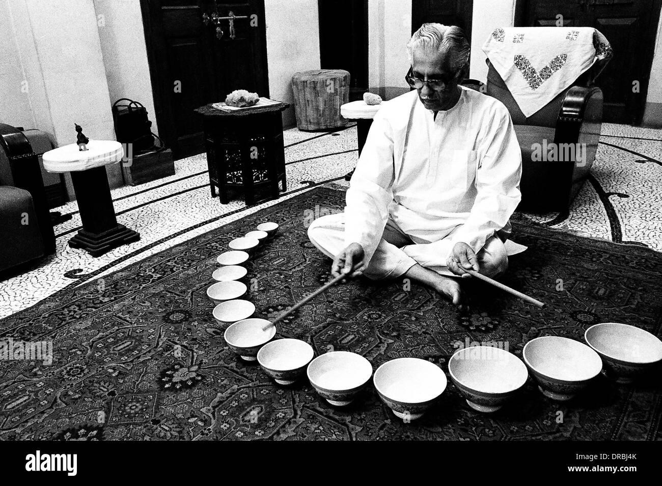 PSI President Ranjit Madhavji playing Jal Tarang melodic percussion instrument striking ceramic bowls with beaters Stock Photo
