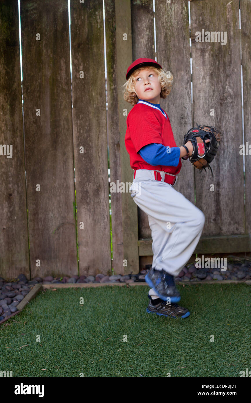 Boy throwing a baseball in the backyard. - Stock Image