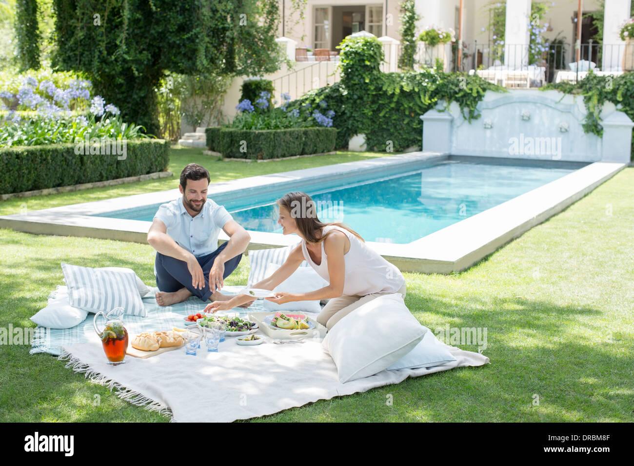 Couple enjoying picnic by pool - Stock Image