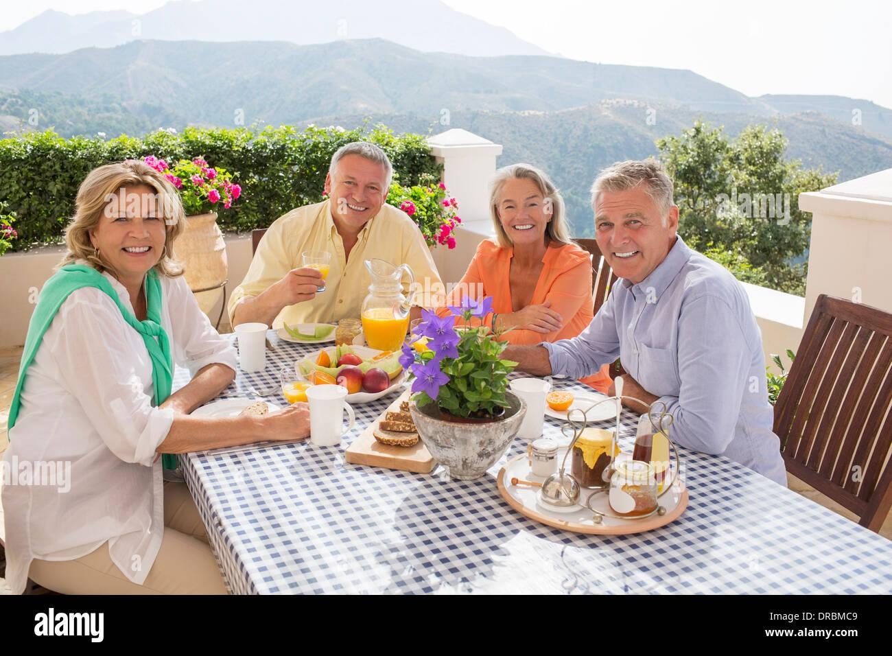 Senior couples enjoying breakfast on patio - Stock Image